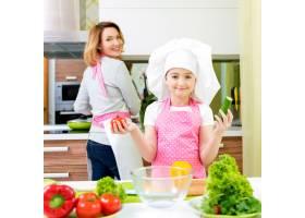 快乐的年轻母亲和穿着粉色围裙的女儿在厨房_11177199