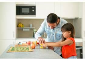 快乐的年轻爸爸和女儿一起享受烹饪女孩和_9649962