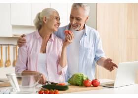 快乐的成熟夫妇家庭使用笔记本电脑和烹饪_7285930