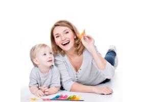 快乐的母亲和躺着的小孩子玩耍的肖像隔离_11554653