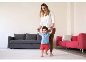 快乐的母亲牵着儿子的手教他走路在长发_11622868