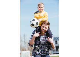 快乐的父亲把他的小儿子扛在肩上_7927353