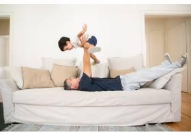 快乐的父亲躺在沙发上抱着儿子_9988347