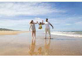 快乐的父母和小女孩喜欢在海滩上散步和活动_10579294