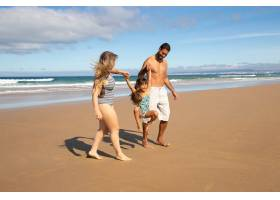 快乐的父母和小女孩穿着泳衣从海上走在金_10608474