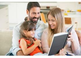 快乐的父母和黑头发的小女孩坐在客厅的沙发_9988379