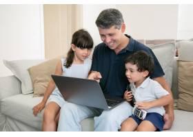 快乐的爸爸向两个好奇的孩子展示笔记本电脑_9988344