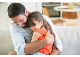 快乐的爸爸和他的小女儿坐在沙发上拥抱着_9988552