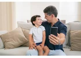 快乐的爸爸和小儿子享受在一起的时光坐在_9988482