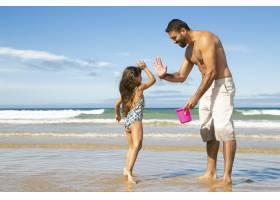 快乐的爸爸和小女儿一起在海滩上用水桶捡贝_10608406