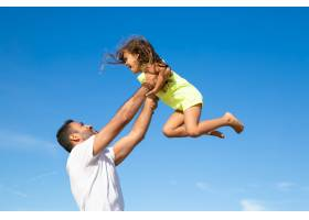 快乐的爸爸抱着兴奋的女孩高高举起双手_11072673