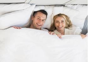 快乐的男人和年轻的微笑的女人盖在毯子里_3544819