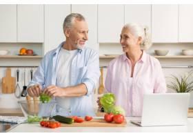 成熟的情侣家庭使用笔记本电脑和烹饪沙拉_7285936