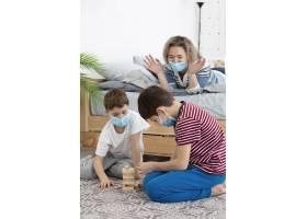 戴着医用口罩的孩子在家里和母亲玩Jenga_7746672