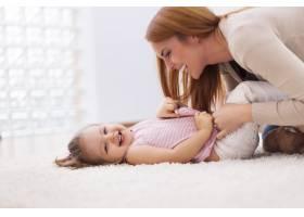 慈爱的母亲在家里的地毯上挠她的小女儿_10979332