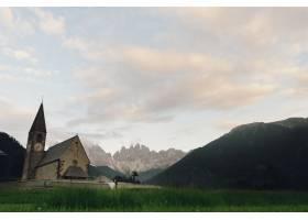 接吻的新人站在山上的石头教堂前_3342122