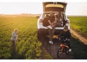带着孩子开车旅行的年轻家庭在田野里停了_8380516