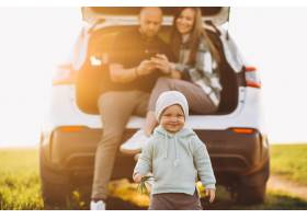 带着孩子开车旅行的年轻家庭在田野里停了_8380519