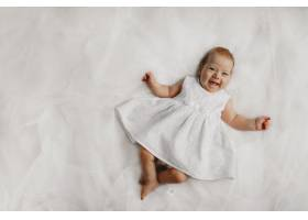床上穿着白色连衣裙的小女婴真诚的微笑_8316246