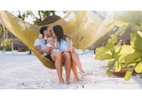 带着小女儿的年轻家庭在海边度假_5175747