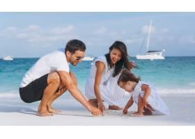 带着小女儿的年轻家庭在海边度假_5175771