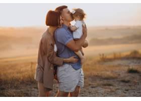 带着小女儿的年轻家庭坐在田野里的夕阳下_10298363
