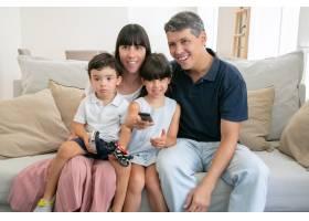 开心的家庭夫妇和两个孩子一起看电视坐在_9988489