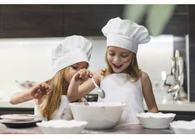 快乐可爱的兄弟姐妹在厨房的工作台上做饭_3775937