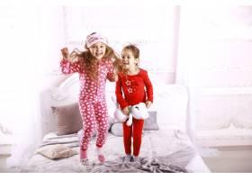 快乐有趣的孩子们穿着鲜艳的睡衣在床上跳来_7250332