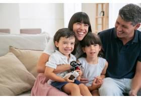 快乐有趣的父母和两个孩子在家看滑稽电影_9988358