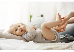 可爱的新生儿躺在床上一边看一边看着妈妈_8811581