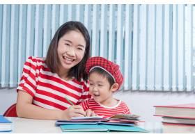 可爱的男孩和他的妈妈一起做作业在家里_1285562