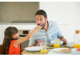 可爱的黑发女孩把一片食物给她的父亲品尝和_9988384