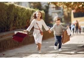 城市里提着购物袋的可爱小孩子_6238759