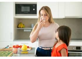 妈妈和女儿一边喝水一边挤柠檬汁一起在_9650473