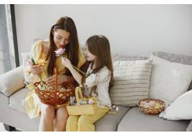 妈妈和女儿穿着黄色的衣服在家里的沙发上准_13272761