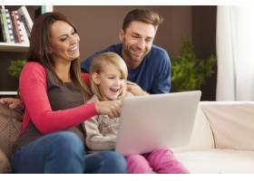 家人一起欢笑在家里使用笔记本电脑_11100490