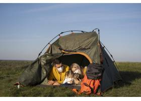家人戴着口罩和他们的狗坐在帐篷里_10827230