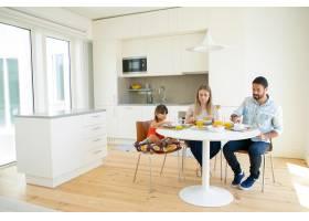 家庭夫妇和孩子一起在厨房里吃早餐坐在餐_9988409
