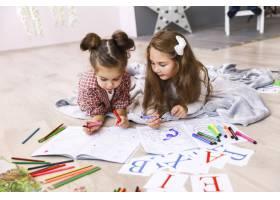两个可爱的小女孩她们正在绘本躺在地上_7250342