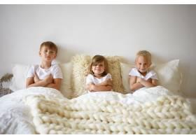 可爱漂亮的女婴在床上两个年长的哥哥之间放_10898065