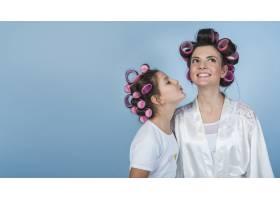 可爱的女儿穿着卷发和浴袍亲吻母亲_3948434