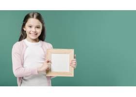 可爱的女孩在摄影棚里和相框合影_2399820