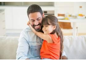 可爱的女孩坐在爸爸的大腿上拥抱他_9988307