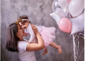 可爱的妈妈抱着她的小女儿温柔地站在房间里_3712815
