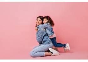 可爱的孩子在粉色背景上拥抱母亲演播室拍_12431978