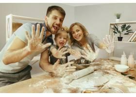 可爱的小女孩和她漂亮的父母在家里的厨房里_12699594