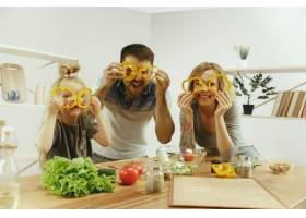 可爱的小女孩和她漂亮的父母在家里的厨房里_12699601