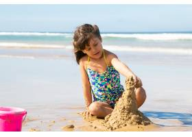 可爱的小女孩在海滩上堆沙堡坐在潮湿的沙_10579141