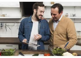 父子俩在厨房里看平板电脑_6881343